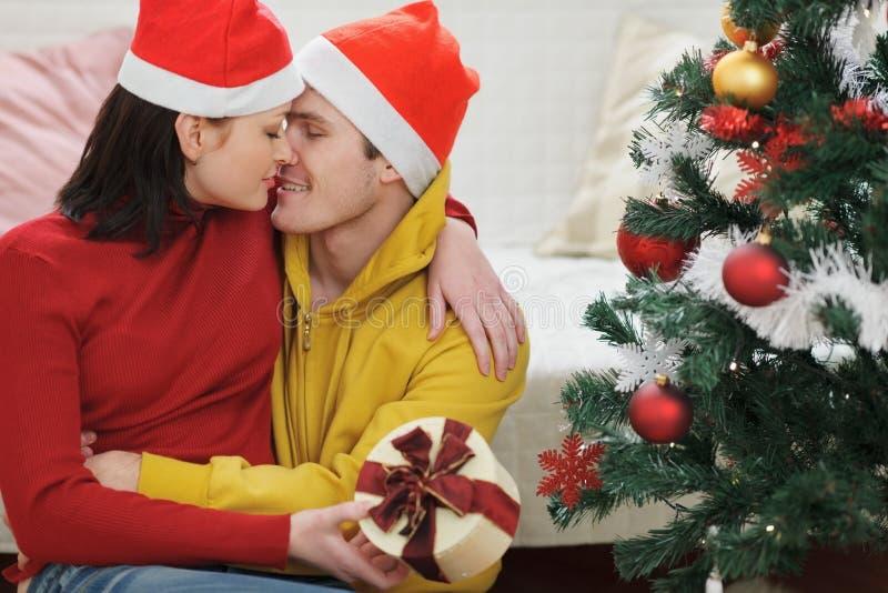Pares jovenes con el regalo que se besa cerca del árbol de navidad foto de archivo