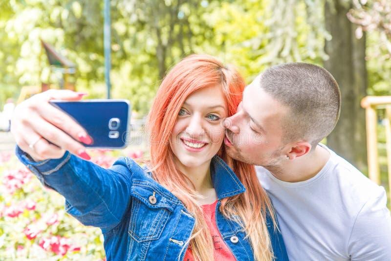 Pares jovenes con el teléfono móvil en el parque fotografía de archivo