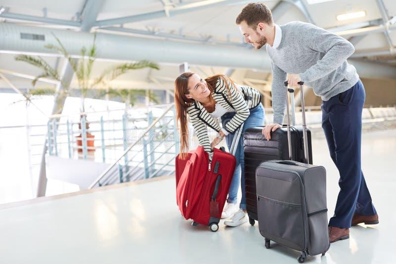 Pares jovenes con equipaje en el terminal de aeropuerto imagen de archivo libre de regalías