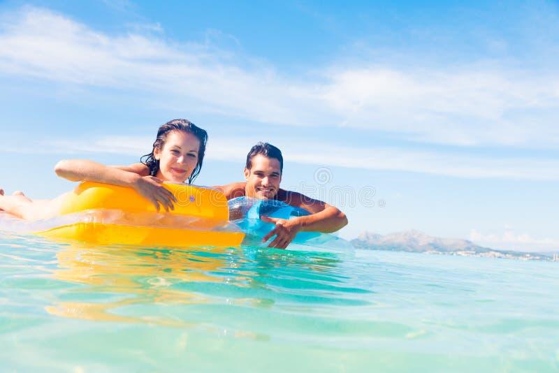 Pares jovenes con la balsa de la piscina fotos de archivo libres de regalías