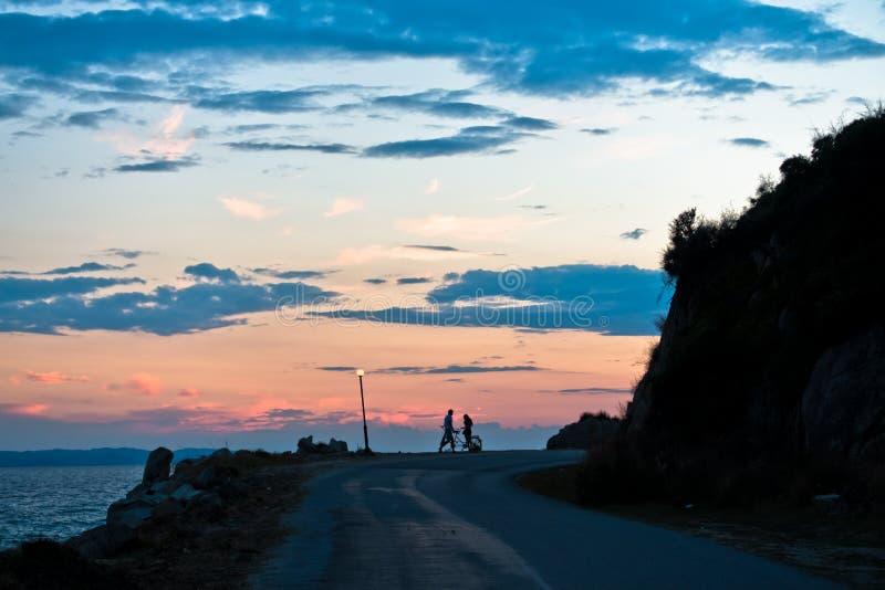 Pares jovenes con la bicicleta en tándem en la costa de mar después de la puesta del sol imagenes de archivo