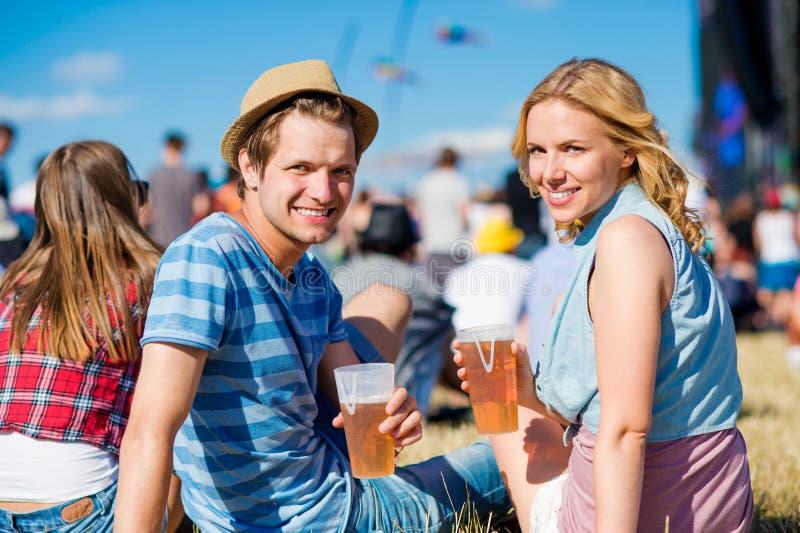 Pares jovenes con la cerveza en el festival de música del verano imagen de archivo
