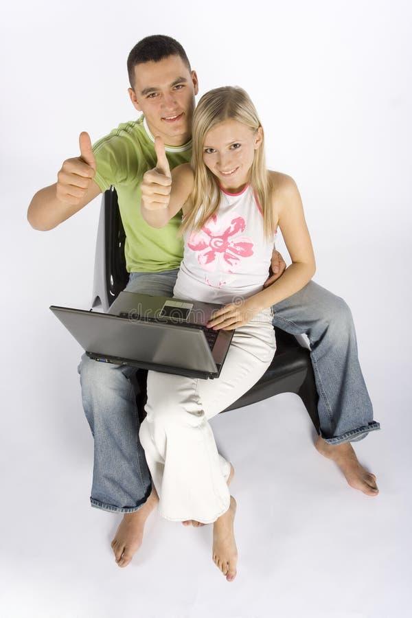 Pares jovenes con la computadora portátil que muestra OK fotografía de archivo