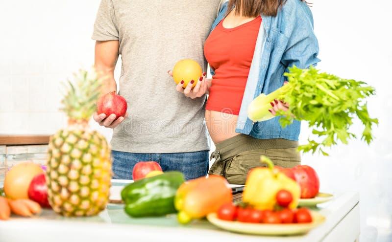 Pares jovenes con la mujer embarazada en el vegano que cocina en cocina fotografía de archivo libre de regalías