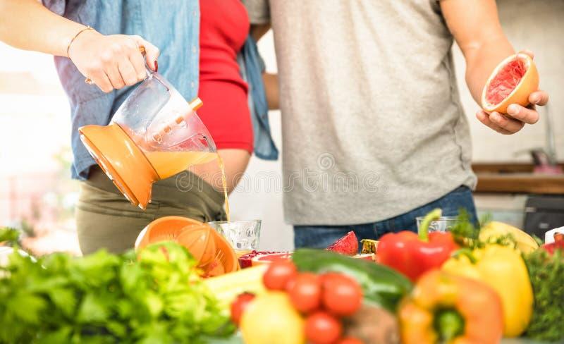 Pares jovenes con la mujer embarazada que cocina la comida vegetariana foto de archivo libre de regalías