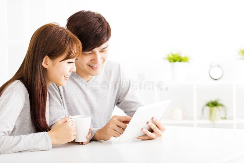 pares jovenes con la tableta en sala de estar fotografía de archivo