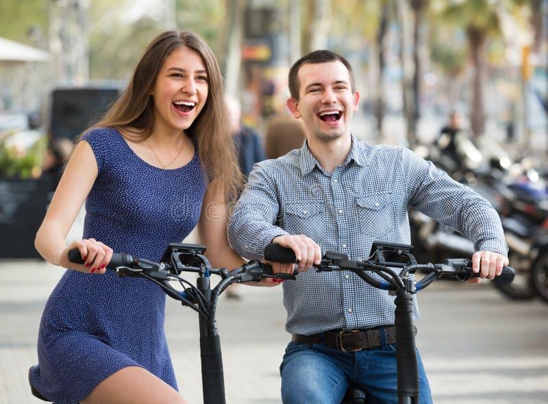 Pares jovenes con las bicis eléctricas fotos de archivo libres de regalías