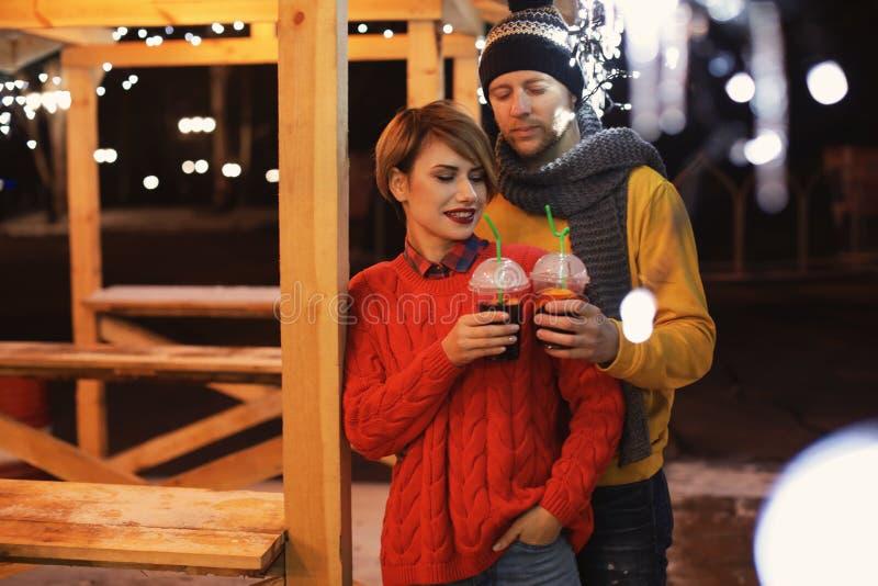 Pares jovenes con las tazas de vino reflexionado sobre en el invierno foto de archivo libre de regalías