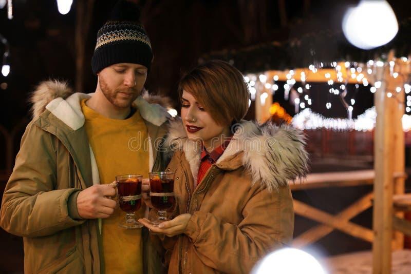 Pares jovenes con las tazas de vino reflexionado sobre foto de archivo libre de regalías