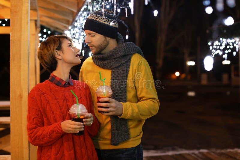 Pares jovenes con las tazas de vino reflexionado sobre en la feria del invierno fotografía de archivo libre de regalías