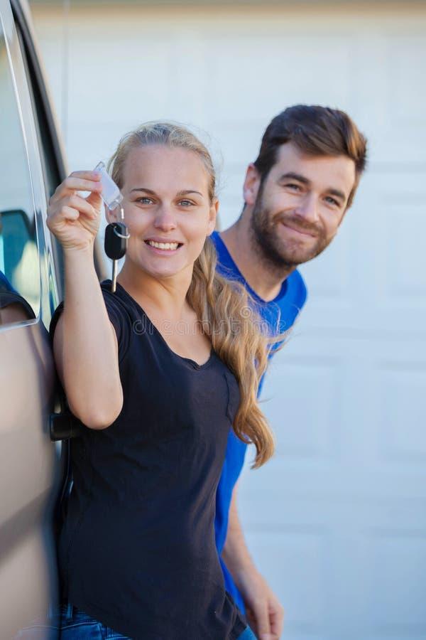 Pares jovenes con llaves al nuevo coche fotos de archivo libres de regalías