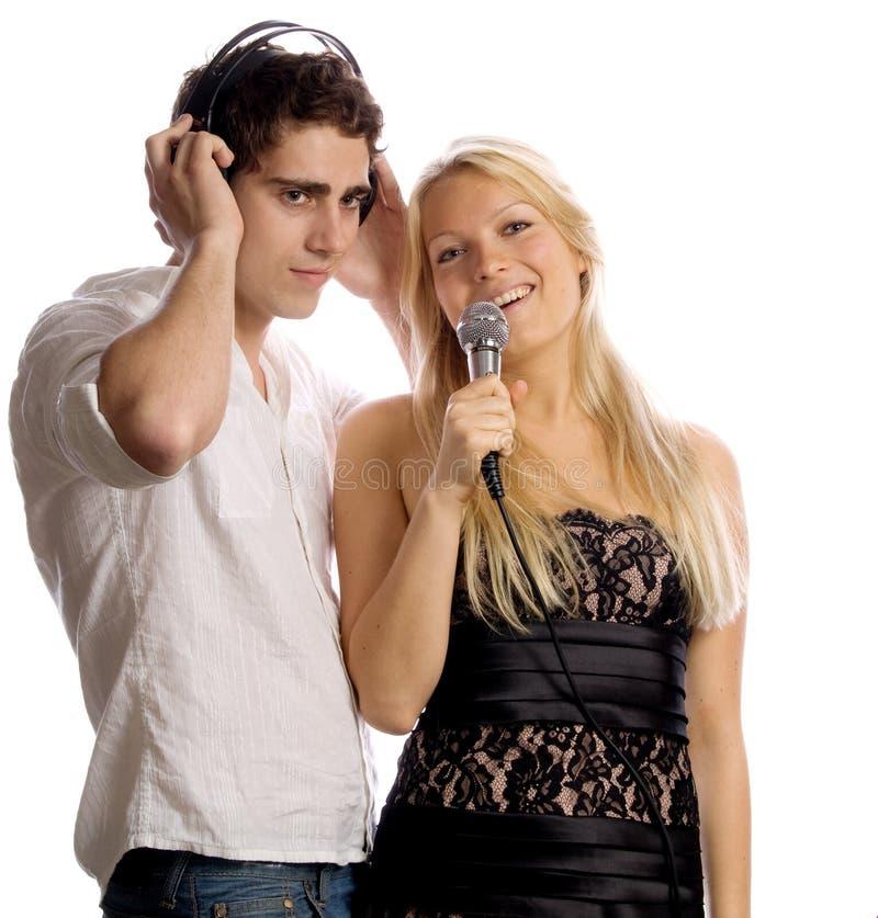 Pares jovenes con los auriculares y el micrófono fotografía de archivo