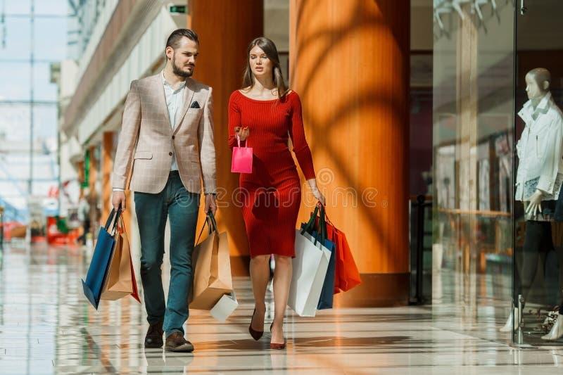 Pares jovenes con los bolsos de compras imagen de archivo