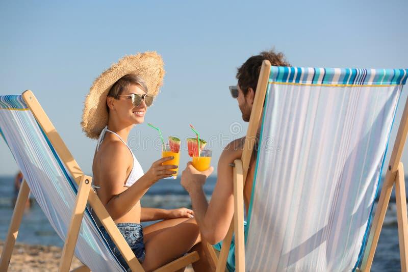 Pares jovenes con los cócteles en sillas de playa fotos de archivo