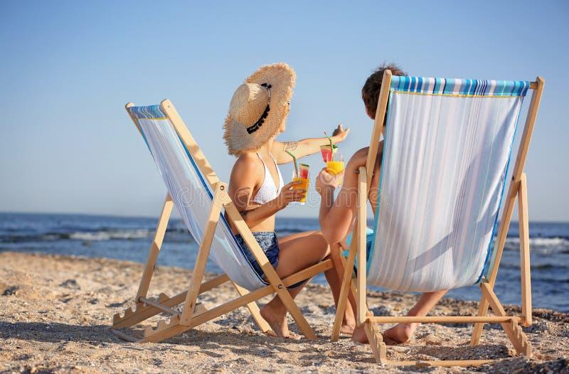 Pares jovenes con los cócteles en sillas de playa imagen de archivo libre de regalías
