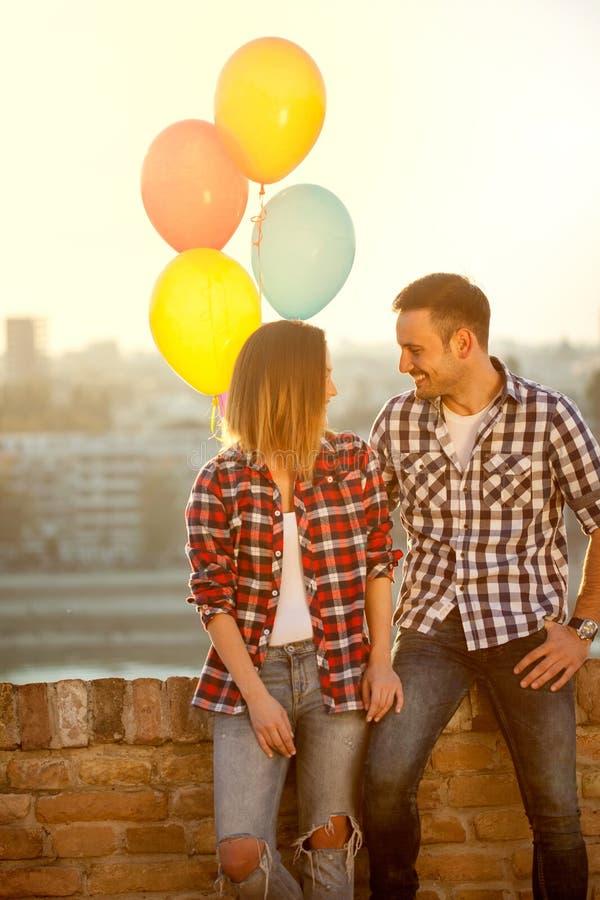 Pares jovenes con los globos que se aman al aire libre fotos de archivo libres de regalías