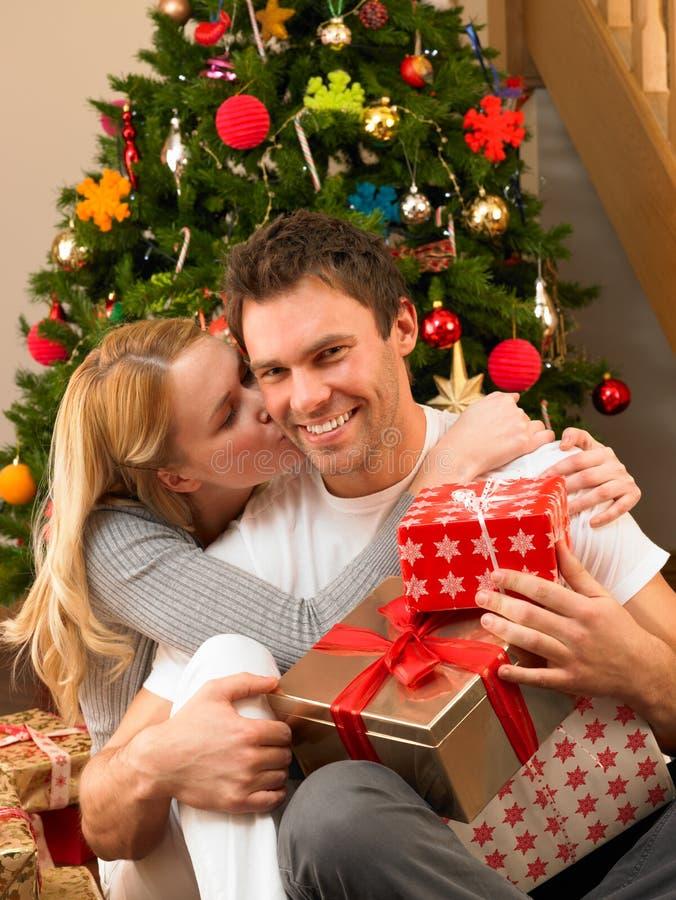 Pares jovenes con los regalos delante del árbol de navidad foto de archivo