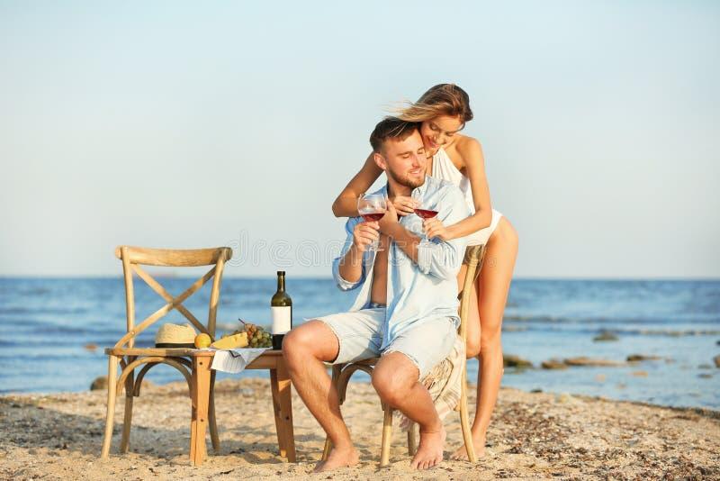 Pares jovenes con los vidrios de vino que cena romántico imagen de archivo
