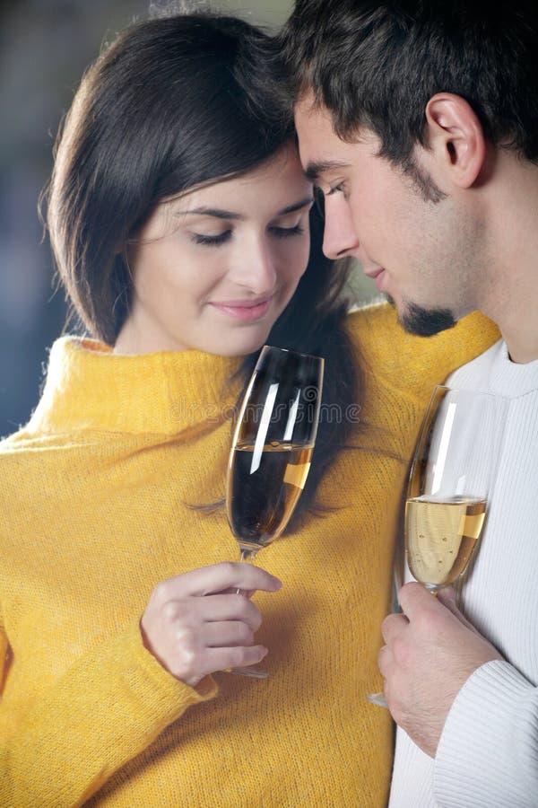 Pares jovenes con los vidrios del champán imagen de archivo