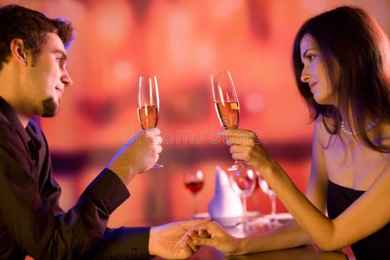 Pares jovenes con los vidrios del champán en restaurante