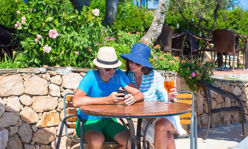 Pares jovenes con smartphone en café al aire libre foto de archivo