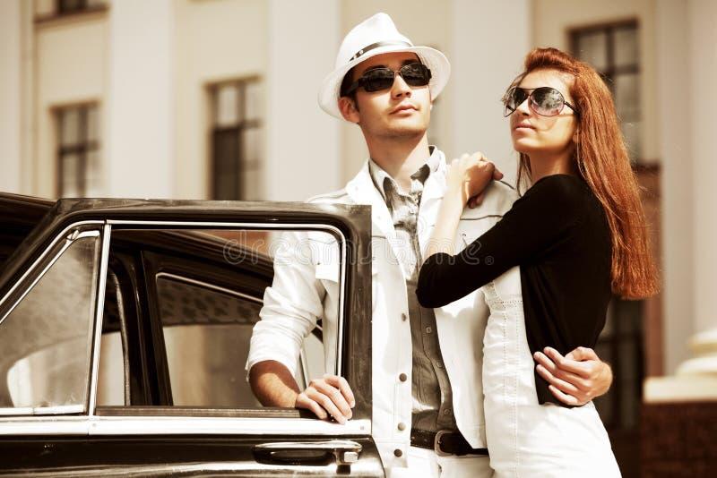 Pares jovenes con un coche retro. fotografía de archivo