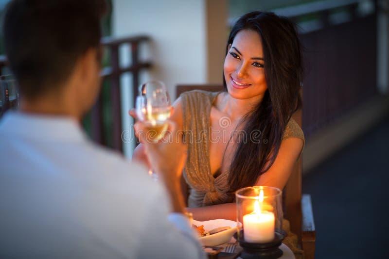 Pares jovenes con una cena romántica con las velas imagen de archivo