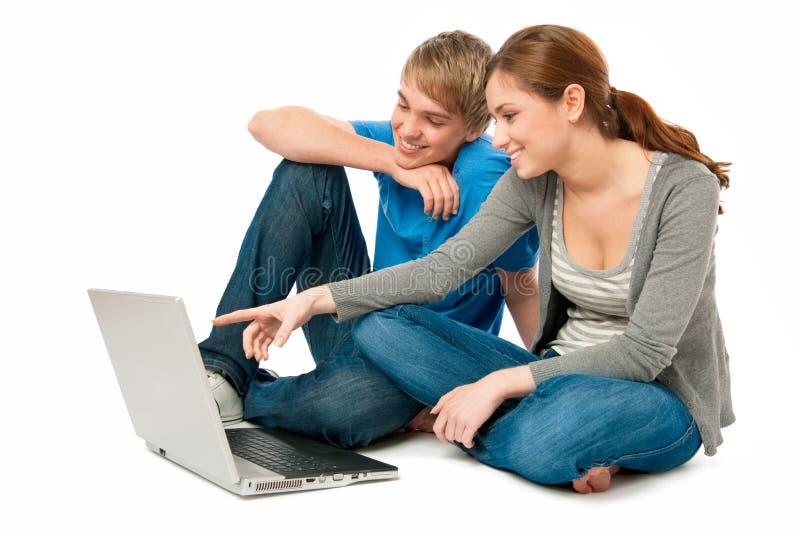 Pares jovenes con una computadora portátil fotografía de archivo libre de regalías