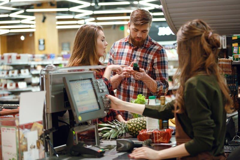 Pares jovenes concentrados que se colocan en supermercado fotos de archivo