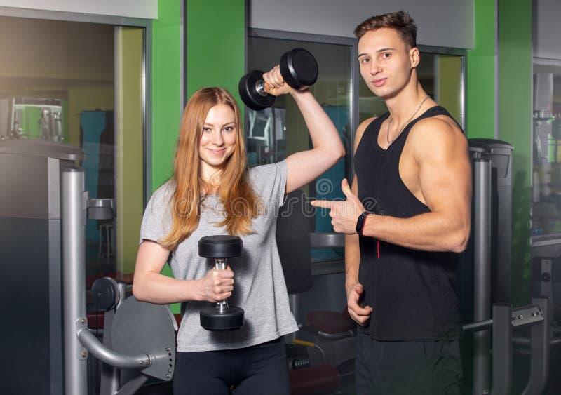 Pares jovenes de atletas en el gimnasio imagenes de archivo