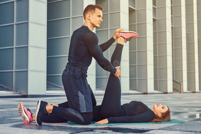Pares jovenes de la aptitud en una ropa de deportes, haciendo estirar mientras que se prepara para el ejercicio serio en la ciuda fotos de archivo libres de regalías