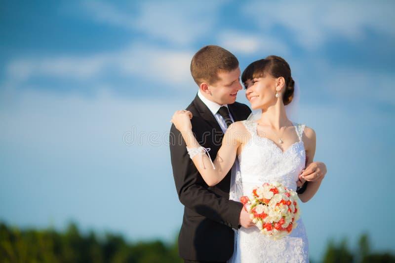 Pares jovenes de la boda - casese recientemente el novio y a la novia que presentan outdoo fotos de archivo libres de regalías