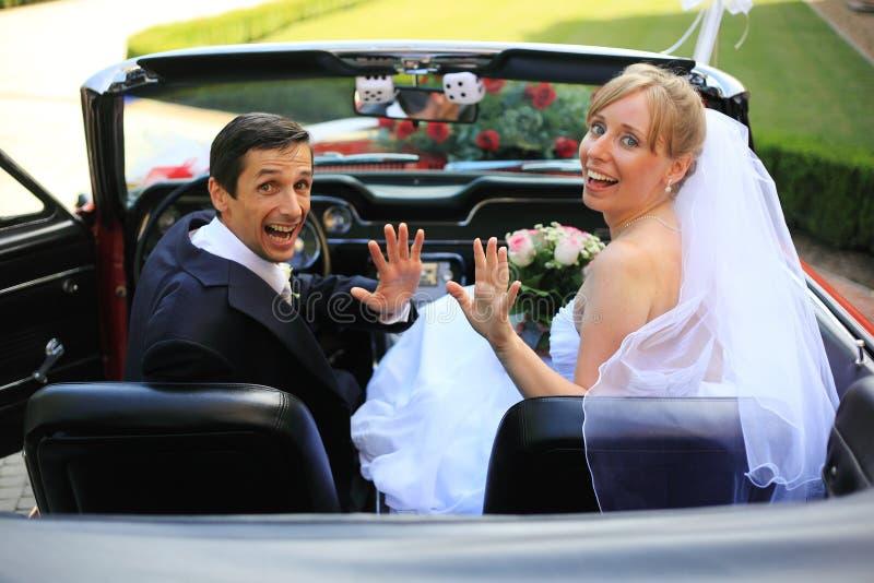 Pares jovenes de la boda en coche del cabriolé imagen de archivo