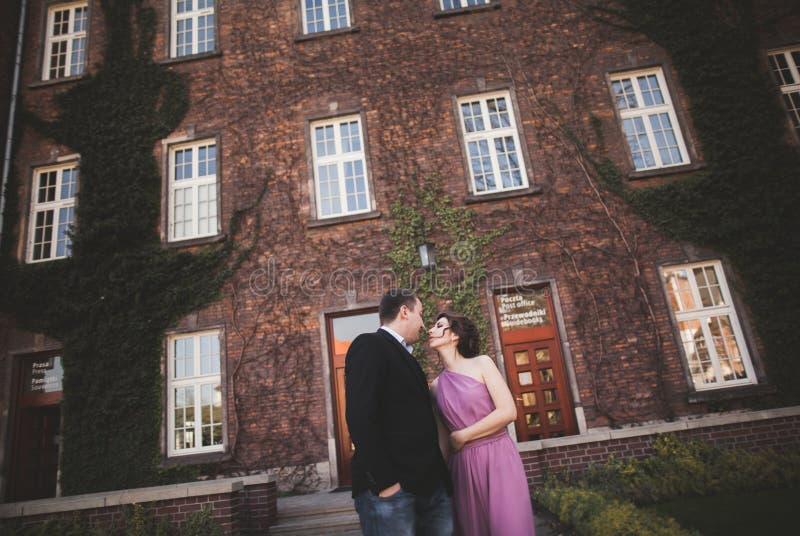 Pares jovenes de la boda en la historia de amor, la novia y el novio presentando cerca del edificio en el fondo kraków imagen de archivo
