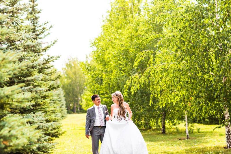 Pares jovenes de la boda que caminan al aire libre fotos de archivo