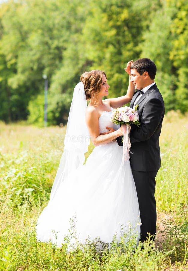 Pares jovenes de la boda que disfrutan de momentos románticos afuera en un prado del verano fotografía de archivo libre de regalías