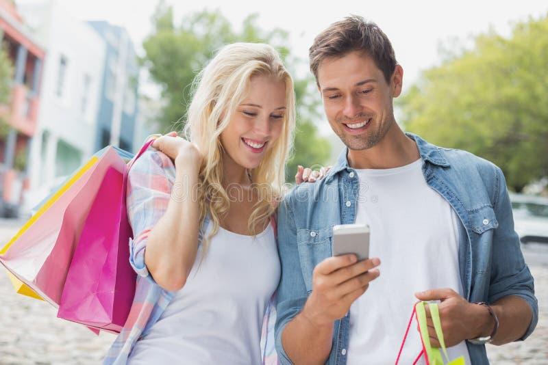 Pares jovenes de la cadera que miran smartphone en viaje de las compras foto de archivo libre de regalías