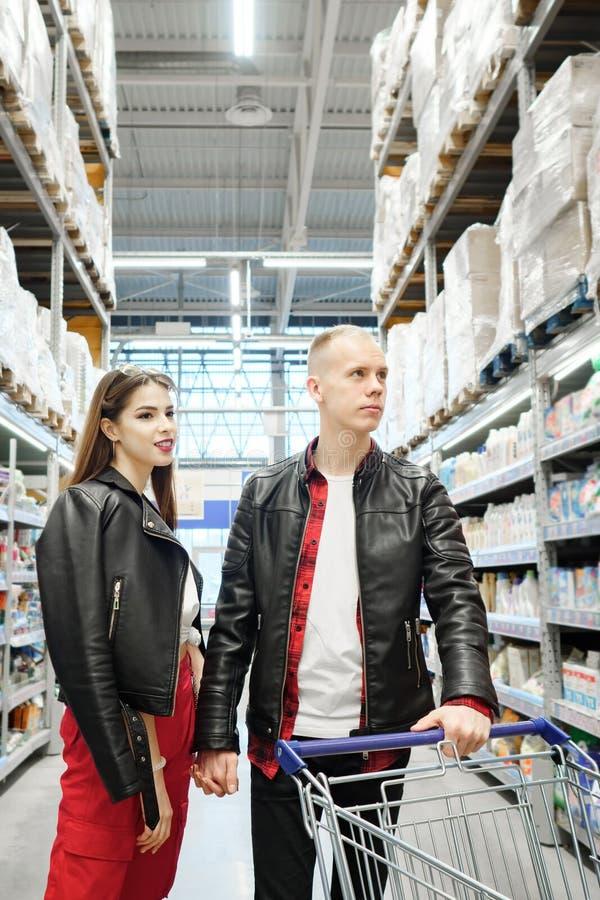 Pares jovenes de la familia que eligen la comida en supermercado durante compras semanales fotos de archivo