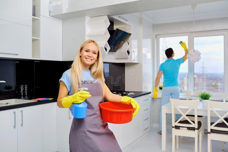 Pares jovenes de la familia que hacen la limpieza en la cocina fotos de archivo libres de regalías