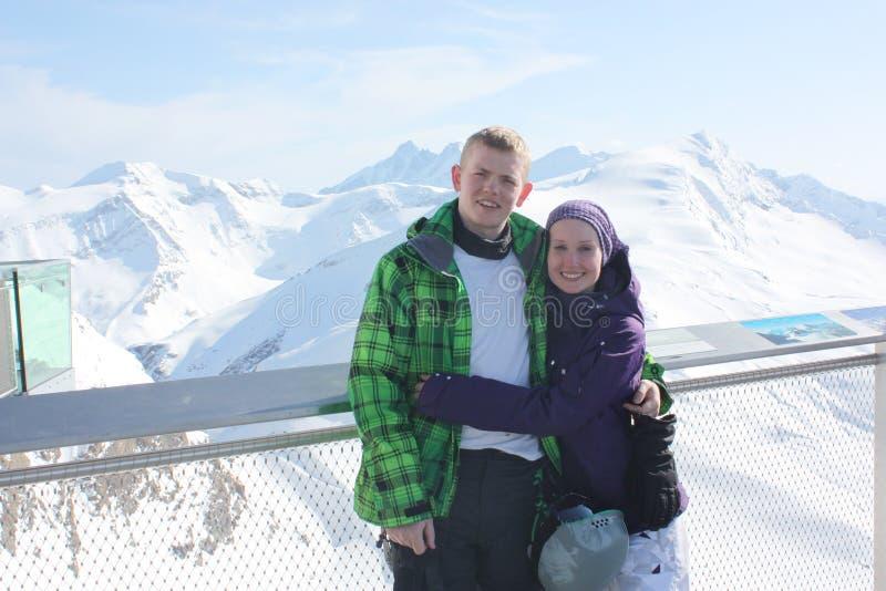 Pares jovenes de la felicidad en el centro turístico de esquí en las montañas imágenes de archivo libres de regalías