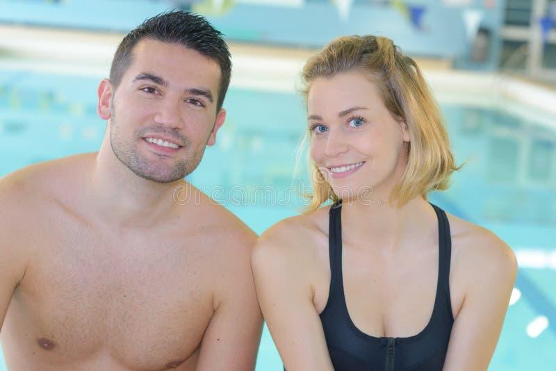 Pares jovenes de la imagen en la piscina fotografía de archivo libre de regalías