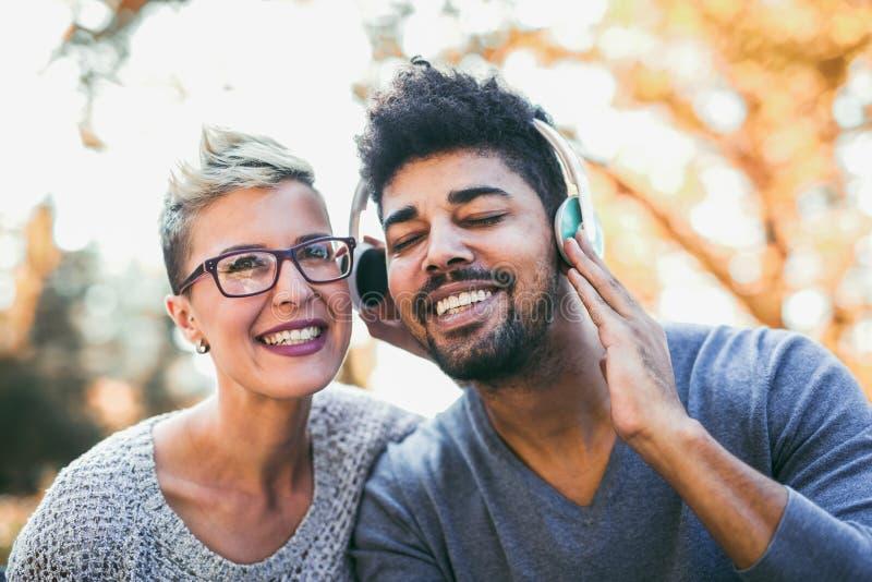 Pares jovenes de la raza mixta que escuchan la música en los auriculares fotografía de archivo