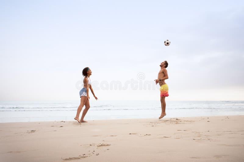 Pares jovenes de la raza mixta que juegan en la playa con fútbol imágenes de archivo libres de regalías