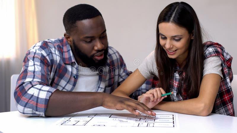 Pares jovenes de la raza mixta que planean el diseño interior de nueva casa, relación imágenes de archivo libres de regalías