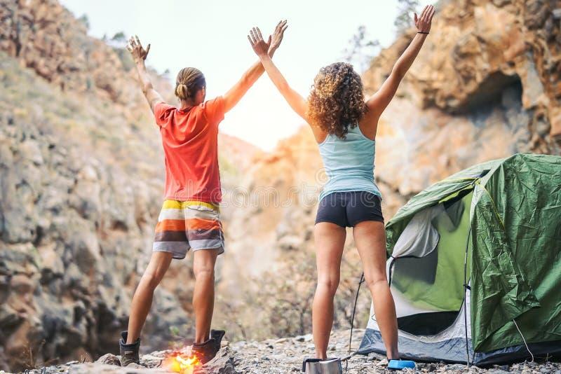 Pares jovenes de la salud que hacen yoga al lado del fuego mientras que acampa con la tienda en una montaña - amigos que meditan  imágenes de archivo libres de regalías