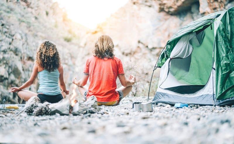 Pares jovenes de la salud que hacen yoga al lado del fuego mientras que acampa con la tienda en una montaña - amigos que meditan  foto de archivo