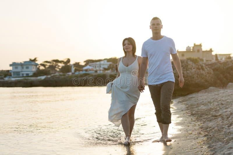 Pares jovenes de las vacaciones que caminan en la playa junto en el amor que se sostiene alrededor de uno a foto de archivo