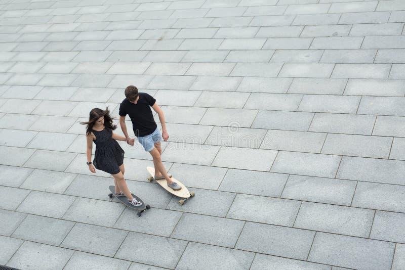 Pares jovenes de longboards elegantes del paseo de los adolescentes foto de archivo libre de regalías