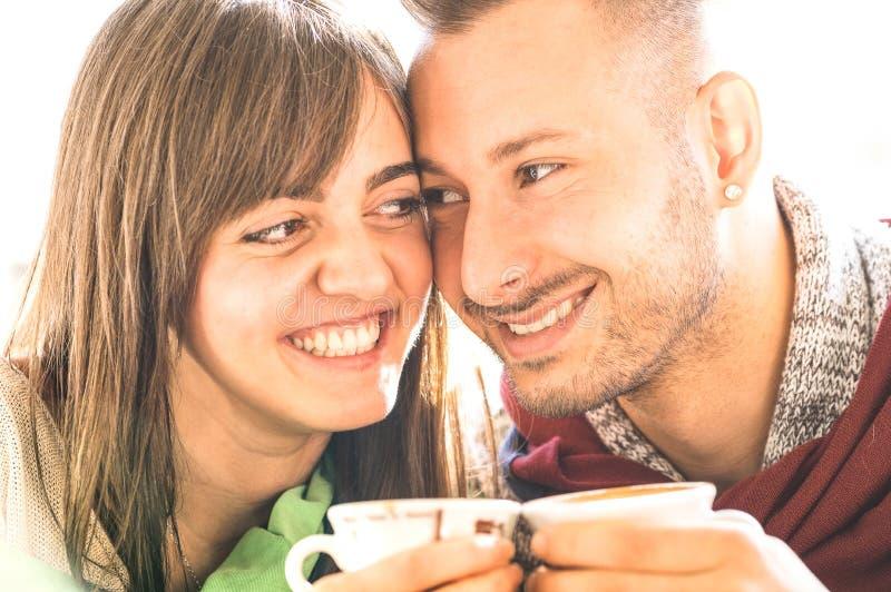 Pares jovenes de los amantes al principio de la historia de amor en la barra de café - capuchino de consumición del hombre hermos imagenes de archivo