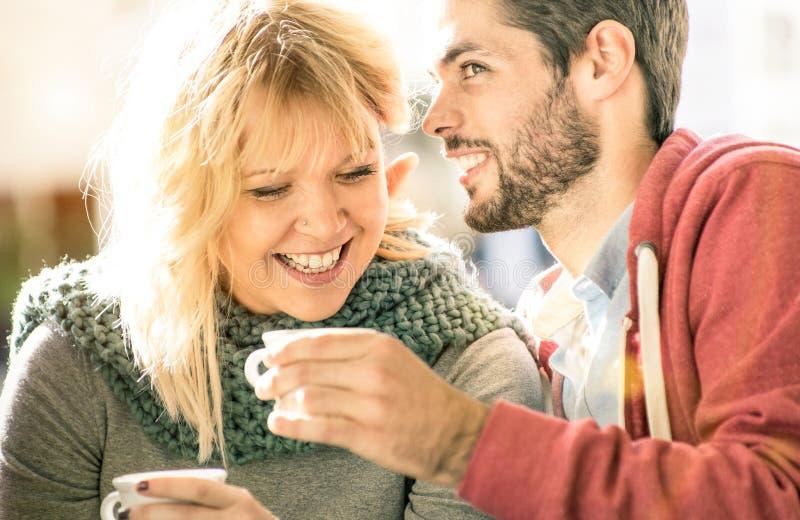 Pares jovenes de los amantes al principio de la historia de amor en barra de café - H foto de archivo